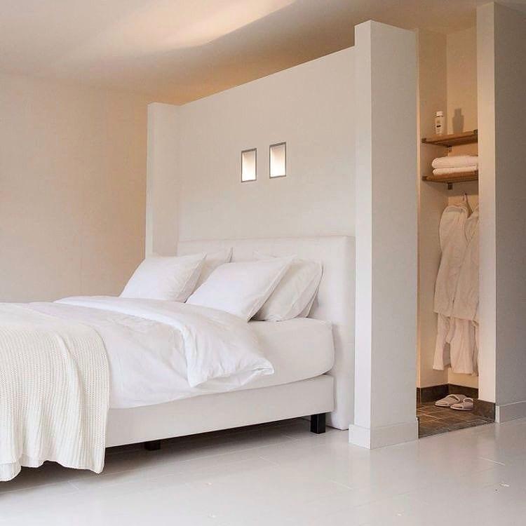 kleines schlafzimmer mit weißem Bett in wandnische einer trennwand und kleines bad mit holzregalen