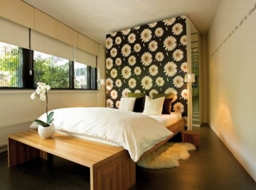 coole schlafzimmereinrichtung mit holzbett, holzbank und weißem fellteppich auf schwarzen betonboden und akzentwand mit blumengemusterter tapette
