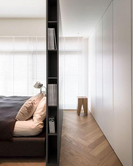kleines schlafzimmer modern einrichten mit grauem Trennelement als Bücherregal, eingebautem Kleiderschrank weiß, parkettboden und weißen Jalousien