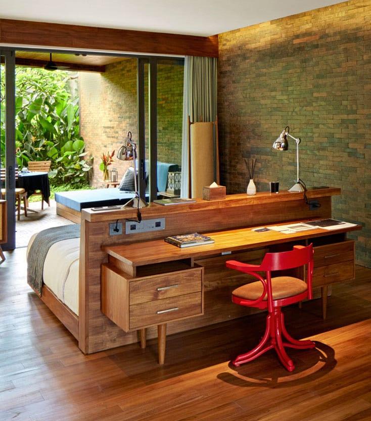 modernes Schlafzimmer mit Parkett, Ziegelwand, überdachtes Terrasse mit schiebefenstertüren und Holzschreibtisch hinterm Holzbett mit Bettkopfteil