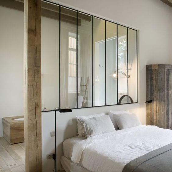 coole gestaltungsidee für kleines schlafzimmer im rustikalen stil mit verglasung zum bad mit holzboden und badewanne mit holzverkleidung