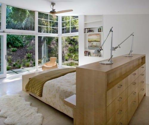 modernes schlafzimmer mit gang zum garten und bett mit kopfteil-kommode aus holz
