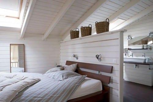rustikales Schlafzimmer unter dachschräge mit trennwand aus holz und kleines bad mit vintage-waschtisch hinterm bett