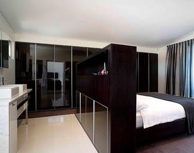 stilvolle schlafzimmer farbgestaltung in schwarz und weiß mit modernem Kleiderschrank in schwarzem Lack und weißem Waschtisch mit zwei waschbecken hinter  schwarzem Bett