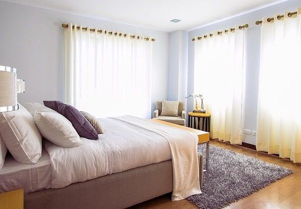 coole farbgestaltung schlafzimmer mit wandfarbe blau, gardinen in beige, box spring bett und dekokissen in lilla und fellteppich grau auf holzbodenbelag