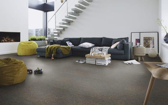 minimalistisches wohnzimmer gestalten mit schwarzem korkboden, ecksofa dunkelblau, puffs grün und diy couchtisch aus Magazinen