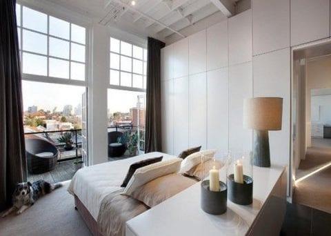 kleines schlafzimmer mit doppelfenstertüren zur terrasse mit eingebautem kleiderschrank und bett mit kommode als kopfteil
