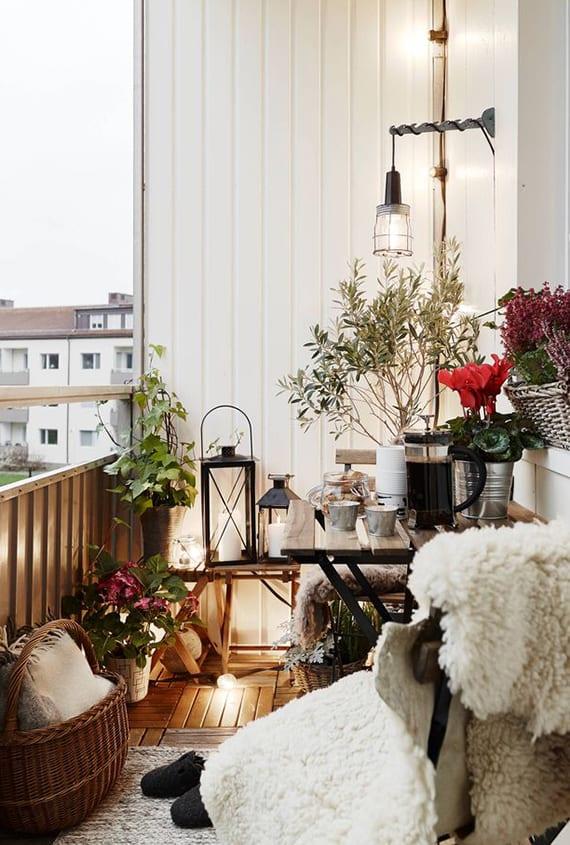 kleiner balkon coole gestalten mit holz-bodenfliesen, schwarzen Laternen aus metall und vintage blumentöpfen
