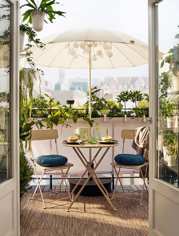 elegante balkongestaltung mit weißen gartenmöbeln aus metall, weißem sonnenschirm mit weißen LED-Kugeln und weißem textil-Sichtschutz