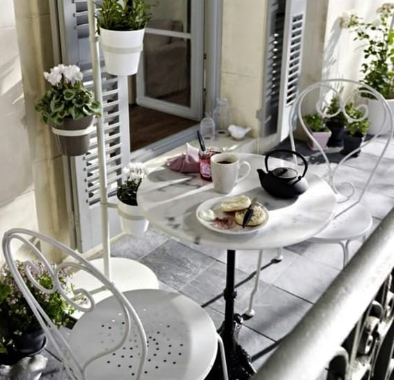 der kleine balkon elegant gestalten mit weißen metallstühlen, kleinem rundtisch, grauen natursteinbodenfliesen, grauen holzladen und blumenständer mit weißen und grauen blumentäpfen