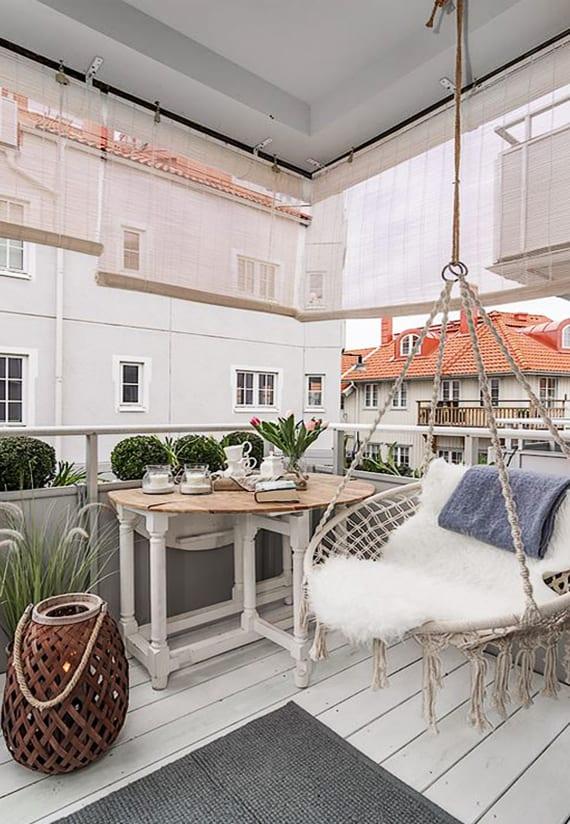 rustikale balkongestaltung in weiß und grau mit rundem Makramee-Schaukelsessel, holzklapptisch, holzbodenbelag und sonnenschutzrollos
