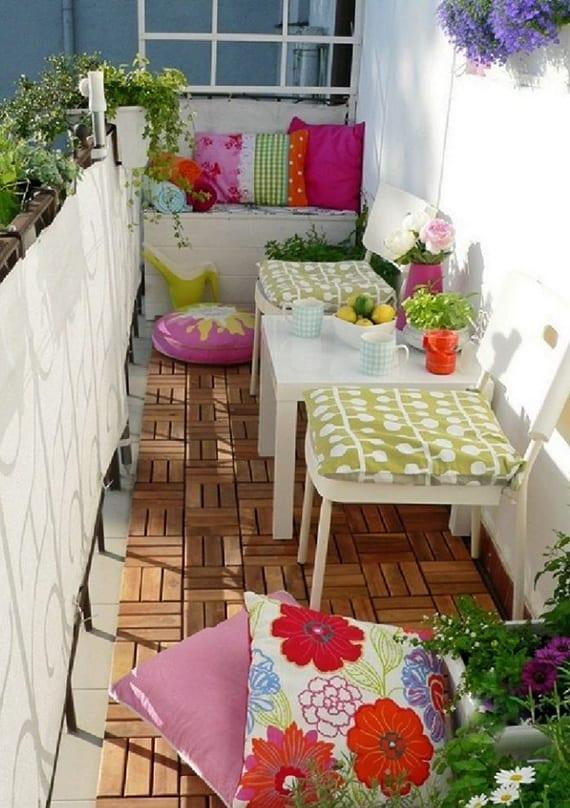 der weiße Balkon bunt gestalten mit dekokissen, weißem kaffeetisch von ikea und weißen stühlen auf holzbodenfliesen