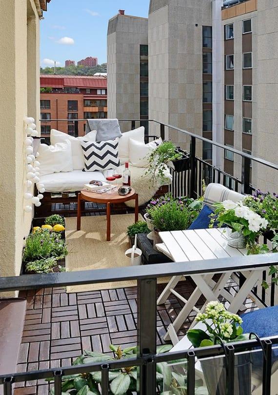 balkon ideen für moderne geataltung mit weißen klapptisch und stühl aus holz, weißen kissen und rundholztisch auf teppich