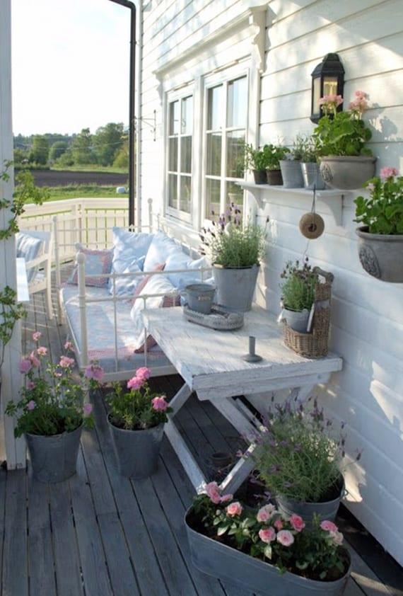 rustikale balkon gestaltung mit bettsofa aus metall und metalleimer-blumentöpfen