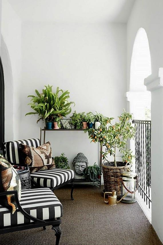 balkon ideen mit gewölbe, metallgeländer, teppich und sesseln mit schwarzweißem Streifenmuster und großem weidenkorb-blumenkonteiner