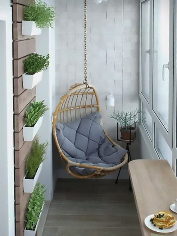 kreatibe gestaltungsidee für kleinen balkon mit holz-schaukelsessel, wanddeko mit holz und weißen blumentöpfen, kleinem Klapptisch aus Holz und weißem wandtapete in 3D optik