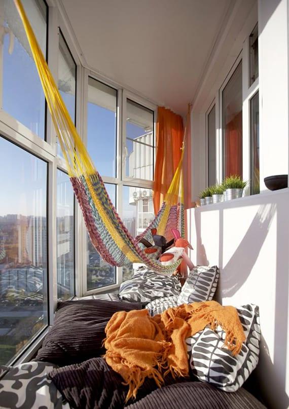 coole balkon ideen für kleine verglaste balkons mit Hängematte, orangen gardinen und grossen bodenkissen