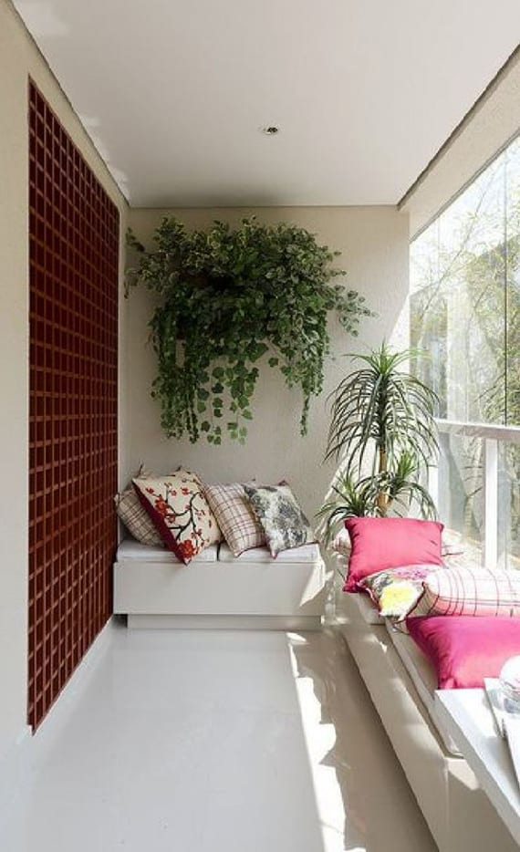 stilvolle balkongestaltung mit weißem bodenbelag, weißen sitzbänken, bunten kissen und holzgitter-wanddeko