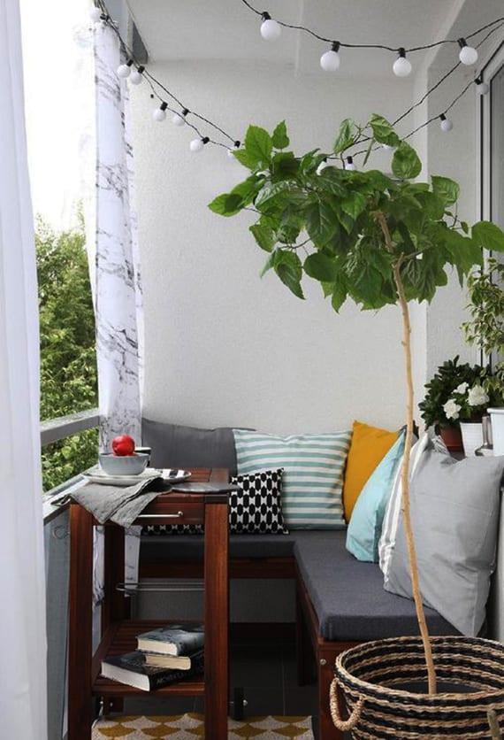 kreative balkon idee für kleine balkons mit sitzecke aus eckbank und kleinem kaffeetisch aus dunkelholz, grauen polstern und kissen