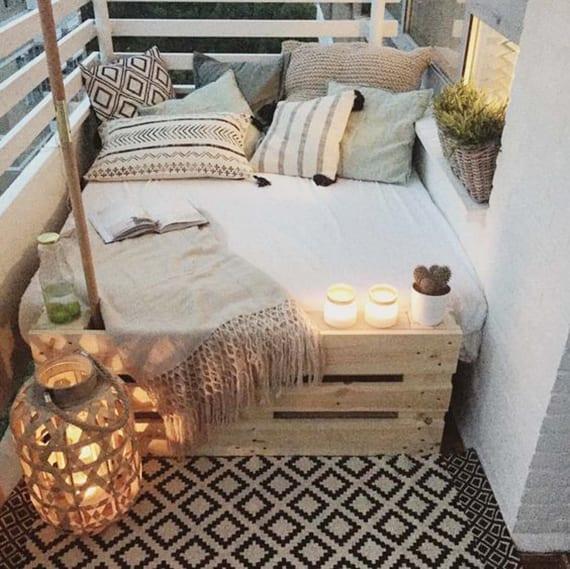 coole balkon ideen für gemütliche Gestaltung mit diy sitzecke, holzlaterne und gemusterten kissen als akzent zu den weißen holzgeländer und ziegelwand