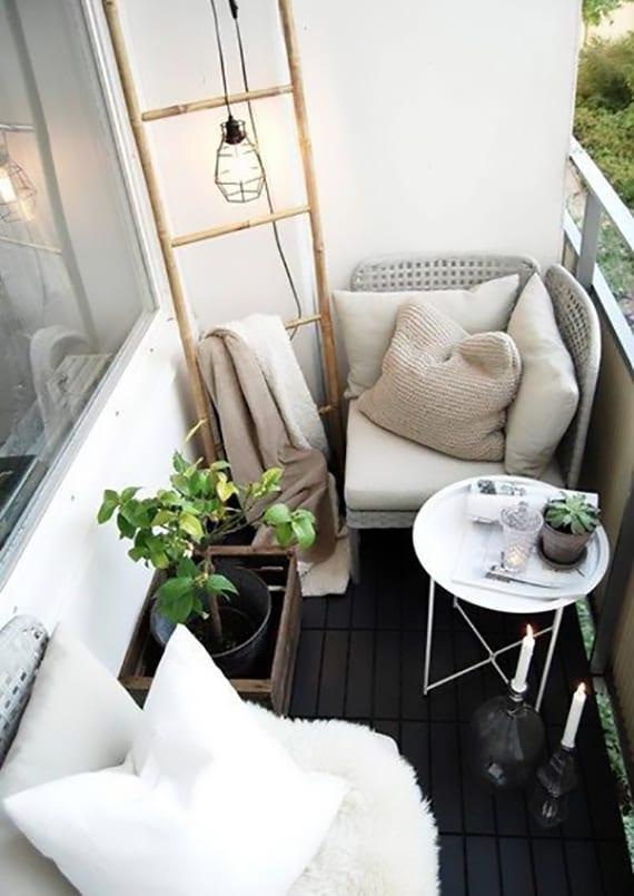 originelle balkongestaltung in weiß und schwarz mit rundem kaffeetisch, diy kerzenhalter und holzleiter als stender für pendellampe