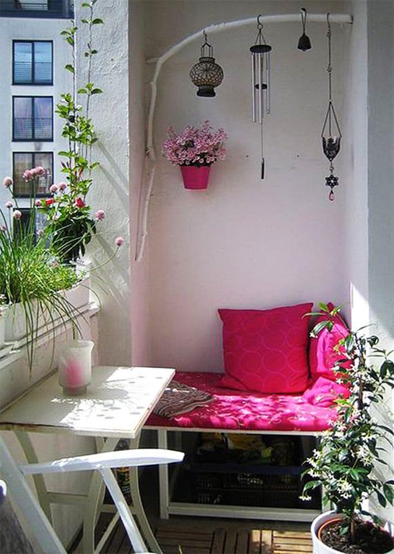 kleines balkon gemütlich und frählich gestalten mit kleinem rustikalem Holztisch weiß, kleine sitzecke mit sitzkissen in pink und kreative DIY Wanddeko mit Zweige