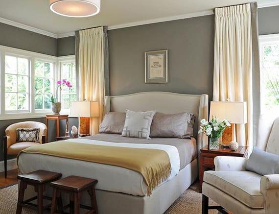 kleines schlafzimmer gemütlich gestalten mit wandfarbe grau, zwei holzhockern, polstersessel beige und bequemem bett mit bettkopfteil und bettwäsche grau