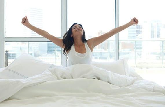 frisch und entspannt aufwachen im bett mit kaltschaummatratze_bett vor glasfassade