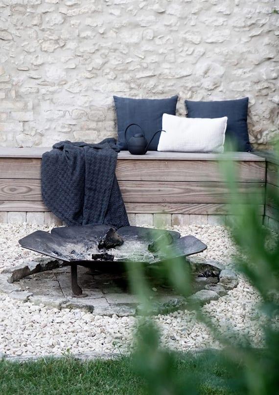 hofgarten modern gestalten mit Kaminecke aus DIY Holz-Ecksitzbank, kiesboden , schwarzer feuerschale und kissendekoration