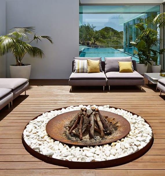 Holzterrasse modern gestalten mit designer Gartenliegen und rundem feuerstelle aus edelstahl und weißen steinen