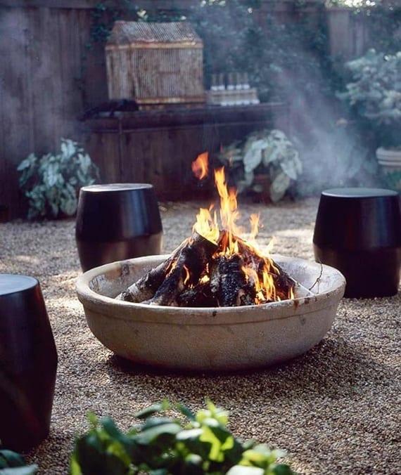 interessante garten idee für gartengestaltung mit kies, runden sitzhockern schwarz und DIY feuerstelle aus Beton