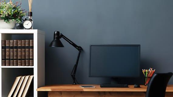 gestaltungsidee für das eigene homeoffice mit wandfarbe schwarz , holzschreibtisch und schwarzer Tischlampe
