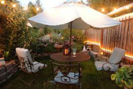 coole gartengestaltung mit gemütlicher Sitzecke unter Sonnenschirm und passende Gartenbeleuchtung mit gluhbirnen und LED-Streifen