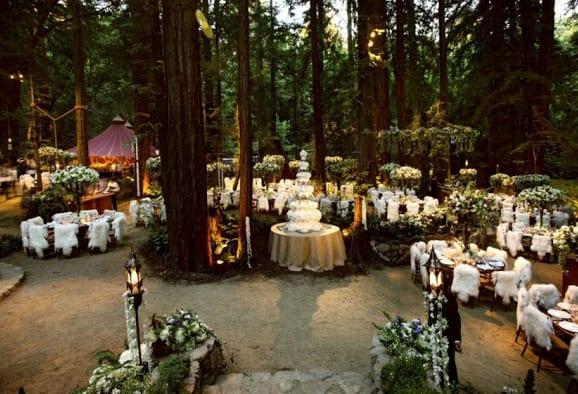 schicke und luxuriöse Sommerhochzeit im wald mit runden Esstischen und Holzstühlen mit weißen pelzdecken