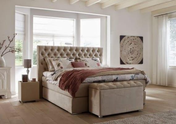 helle und gemütliche schlafzimmergestaltung mit laminat, weißen gardinen und modernem Boxspringbett mit nachttischen und gepolsterter Bank in creme