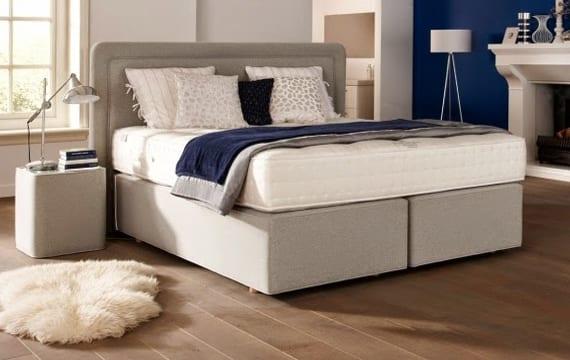 modernes schlafzimmer design mit holzbodenbelag, kamin, akzentwand blau und box-spring-bett mit modernen nachttischen und gepolstertem kopfteil in beige