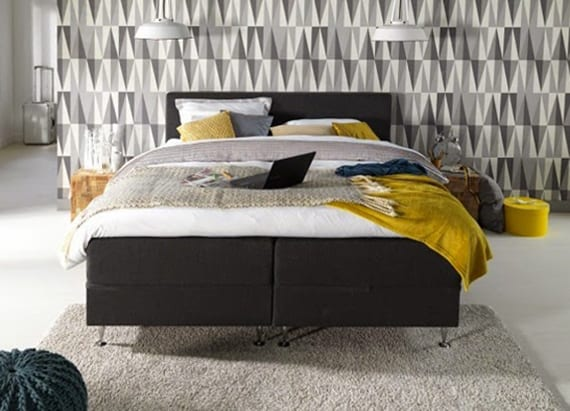 extrem schickes schlafzimmer gestalten mit weißem boden, modernem boxspringbett in anthrazit, vintage pendellampen weiß und cooler akzentwand mit tapete in weißen und grauen dreiecken