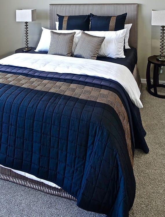 schlafzimmer stilvoll gestalten in blau und grau mit einem box-spring-bett , runden nachttischen schwarz, modernen tischlampen und grauer wandfarbe