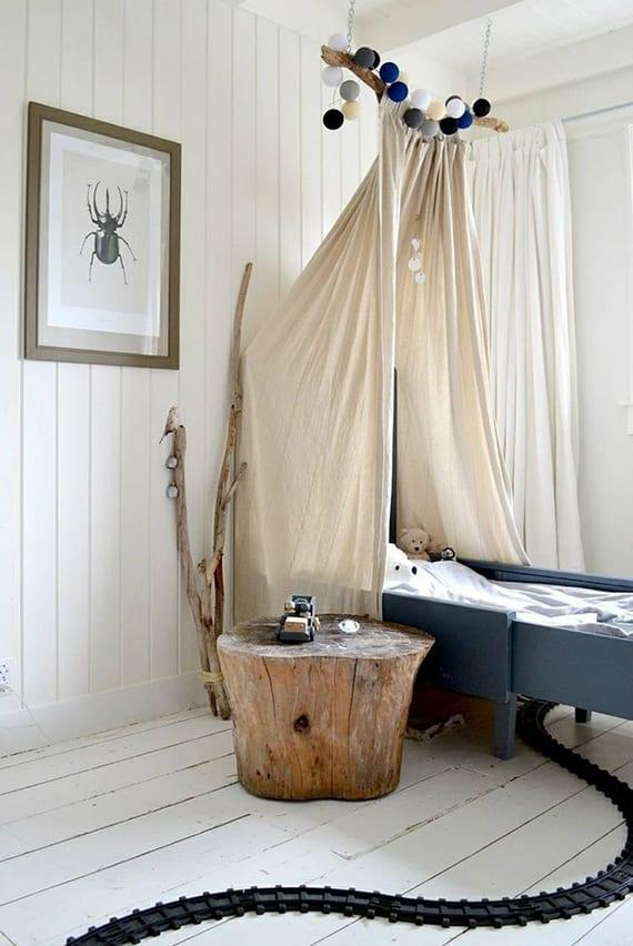 rustikale kinderzimmergestaltung mit himmelbett, weißem holzbodenbelag, baumstamm als nachttisch und treibholz als deko