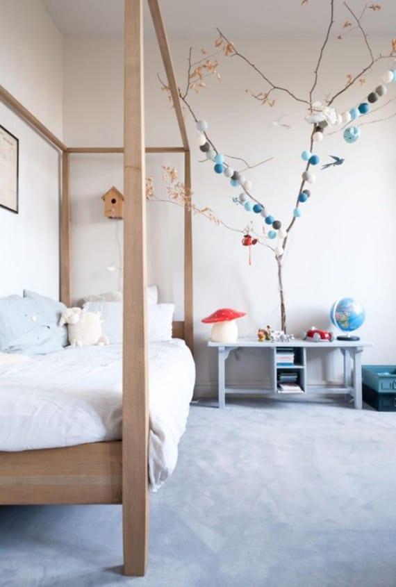 kinderzimmer cool gestalten mit holzbett, zweig mit blauen lkugelleuchten, pilze-tischlampe und vogelhaus über dem bett