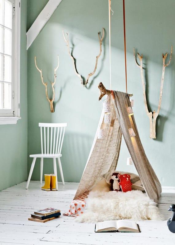 moderne und rustikale kinderzimmergestaltung mit wandfarbe blaugrün, weißem holzboden, diy zelt und wanddeko aus zweigen