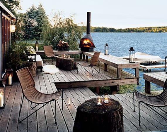 holzterrasse einrichten mit Holzbänken, baumstamm-Kaffeetischen, Rattanstühlen, gartenkamin und schwarzen metalllaternen