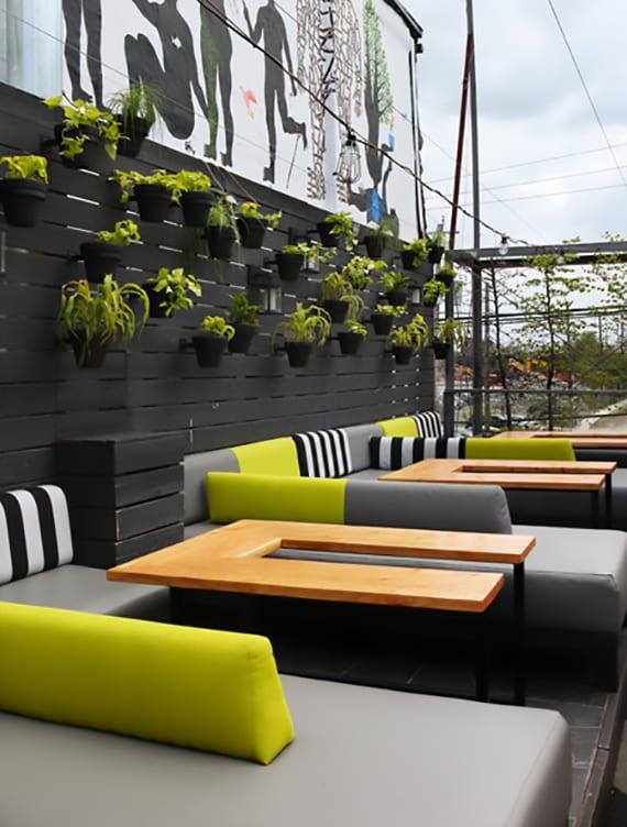 modernes cafe auf der terrasse einrichten mit schwarzer sichtschutzwand aus holz mit schwarzen Blumentöpfen als wanddeko und modernen Sofas in knalligem grün und grau mit u-förmigen holztischen