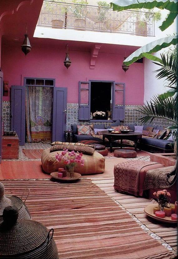 orientalische terrassengestaltung mit wandfarbe pink, lilafarbigen fensterladen, teppichen und sitzkissen