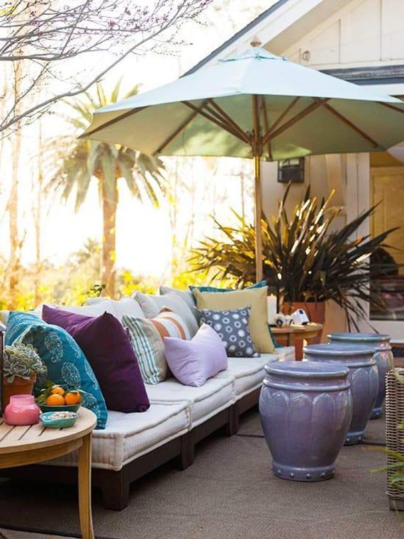 terrasse bunt und modern gestalten mit drei runden marokkanischen hockern in lila, gartensofa mit bunten kissen, weißem sonnenschirm und runden holzbeistelltischen