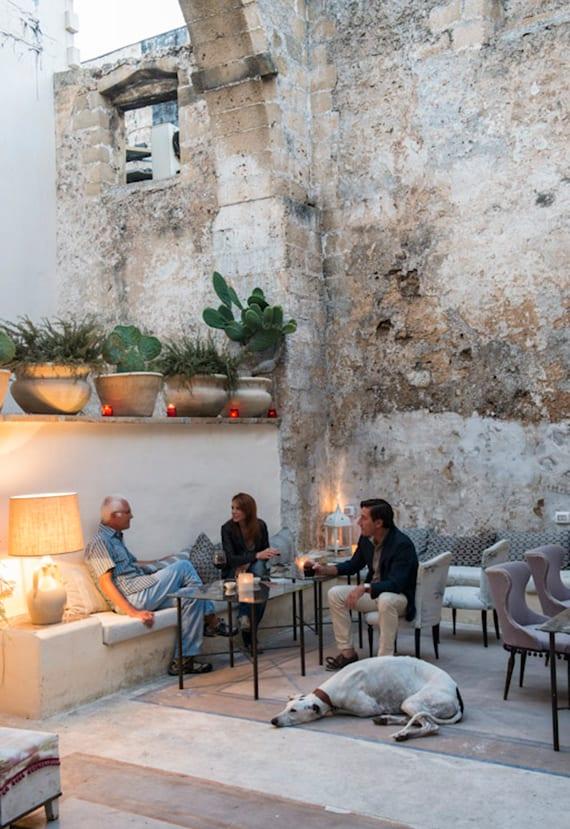 mediterranische terrassengestaltung mit ausgemauerten sintbänken, bunten polsterstühlen und Tischlampen
