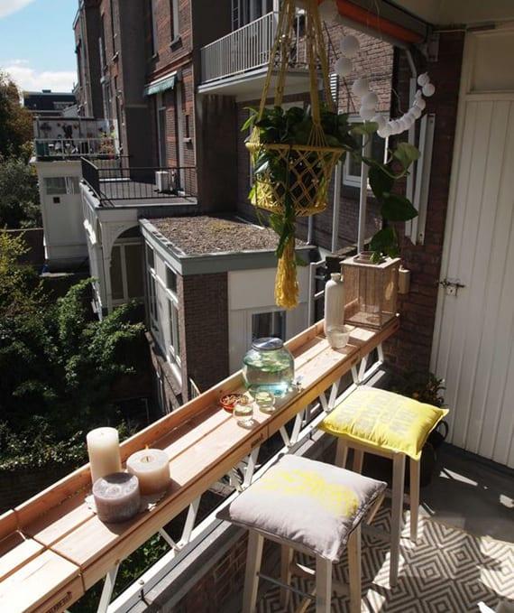 kleine terrasse einrichten mit holzbar, weißen holzhockern mit kissen, kerzen und lichterkette