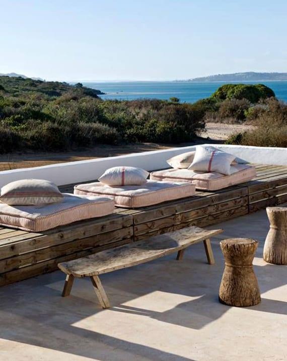 originelle Terrassengestaltung im mediterranischen Stil mit Holzpodest und polstern zum sitzen und liegen