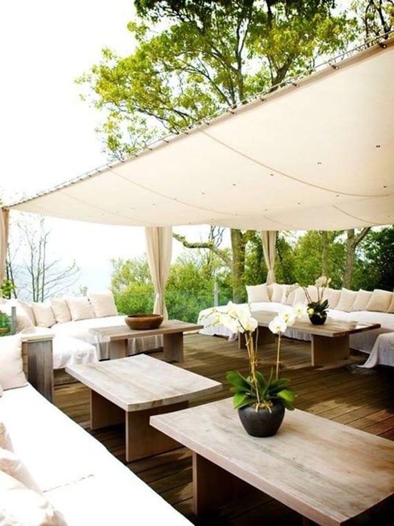 holzterrasse modern gestalten in weiß mit weißen sofas,kissen und gardinen und modernen holzkafeetischen