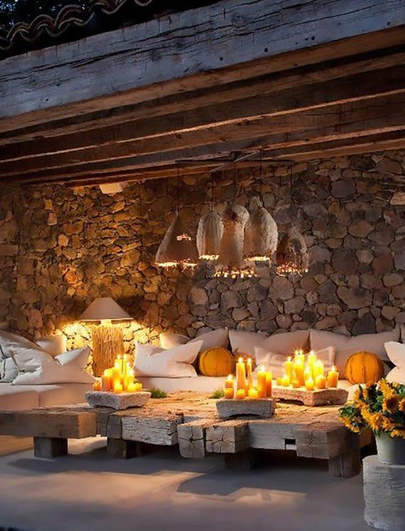 überdachte terrasse mit mauerwand, attraktiven pendellampen, coole kerzendeko auf rustikalem holztisch und moderne sitzecke aus weißen polstern